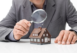 Home inspector with magnifying glass over a home.