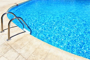 A close up of a crystal clear swimming pool with a ladder to get out and a brick pool area.