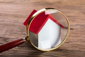 Magnifying glass over a toy home on a wood grain background.