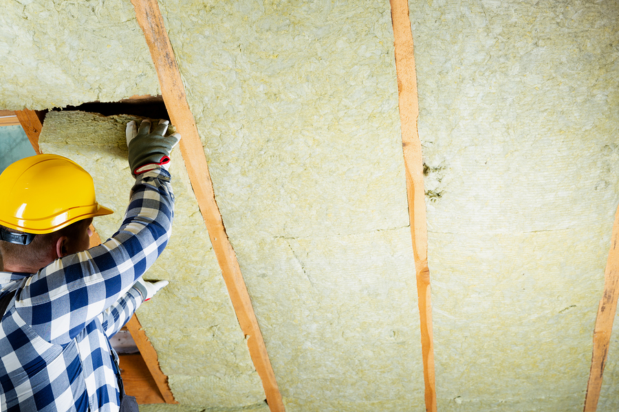 The roof of a home being installed with insulation by a worker