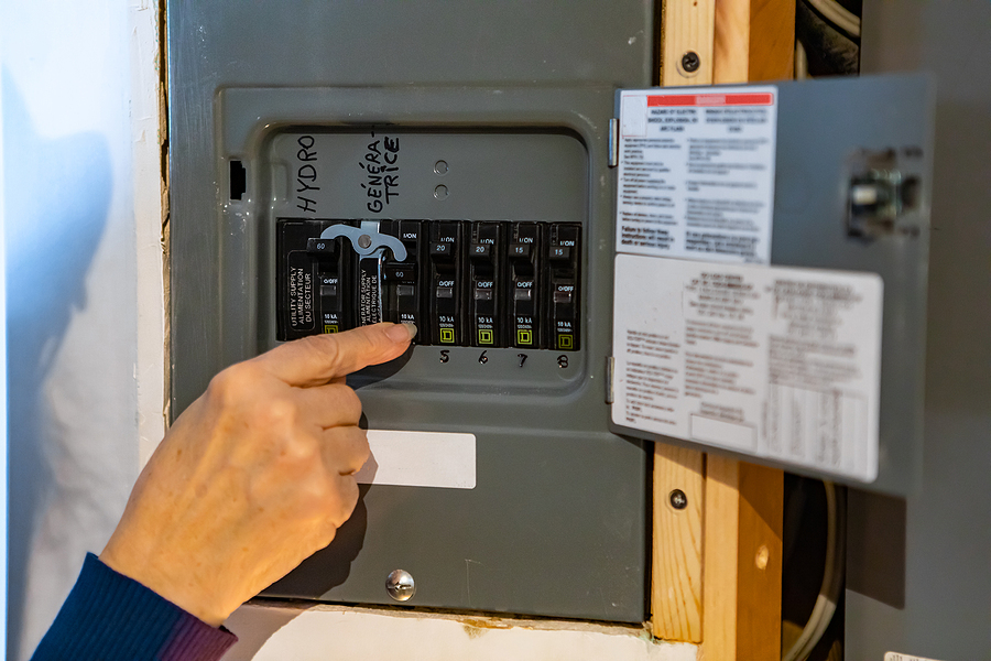 A woman's hand touching a switch in a fuse box.