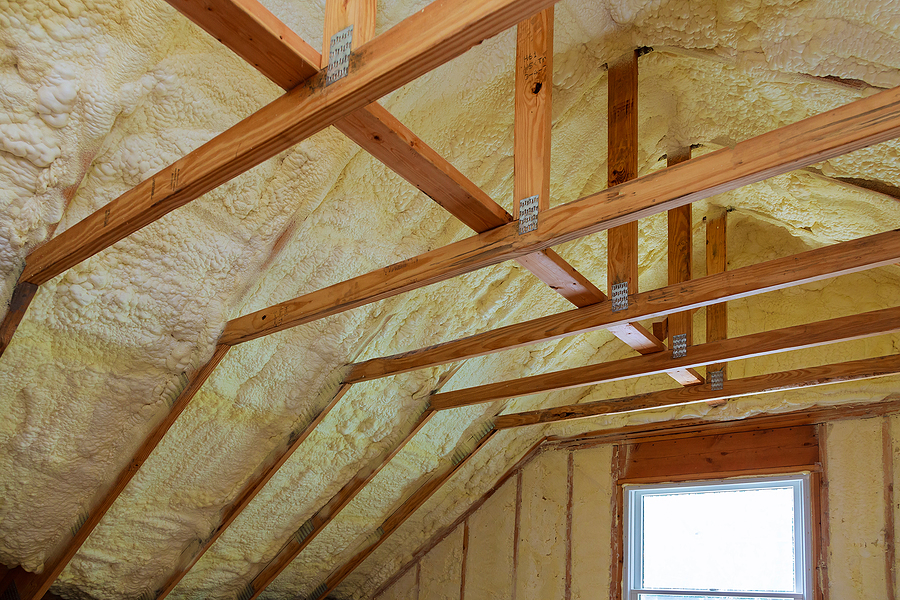 An insulated attic with cross-support beams, trusses, and a window, meant to portray common problems found in attics and crawlspaces.