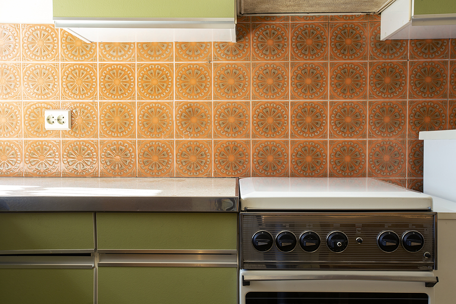 A 1970s vintage retro kitchen with an outdated oven, green cabinets, and orange wall tiles.