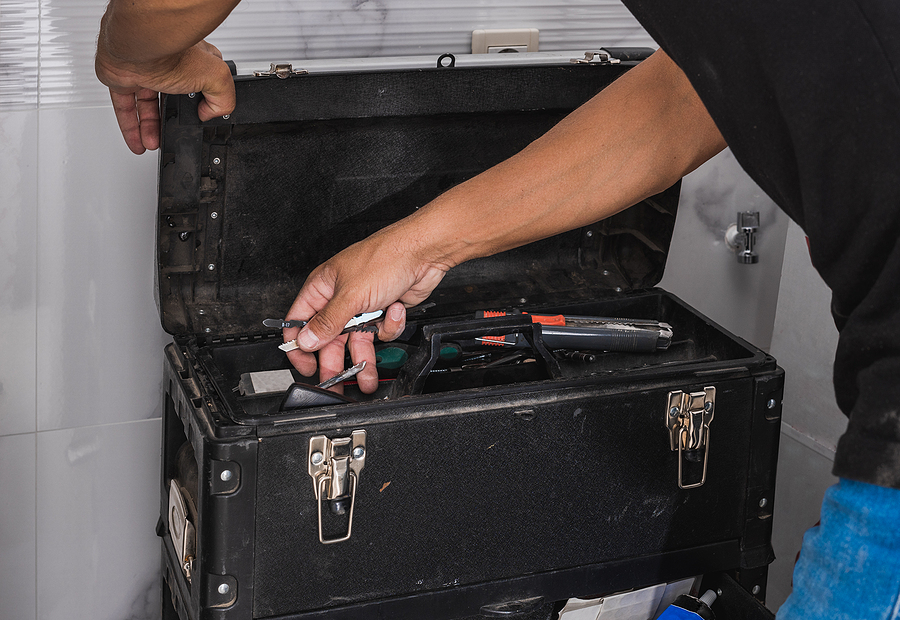 A home inspector reaching into a black metal toolbox.
